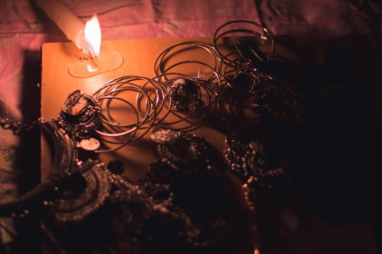 High angle view of jewelry by burning candle on wooden board