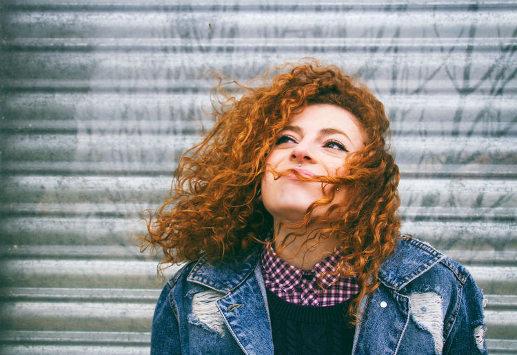 Close-up of young woman with curly hair against shutter