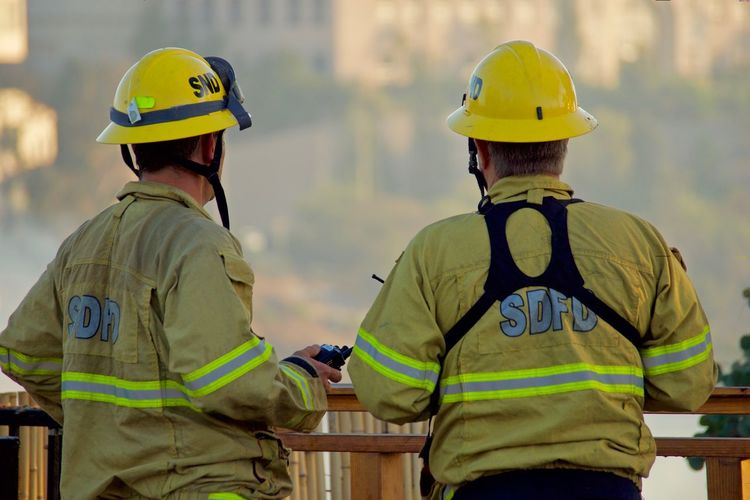 Firefighters looking out at the blaze Clothing Cooperation Day Firefighter Focus On Foreground Headwear Helmet Men Occupation Outdoors Protection Protective Workwear Real People Rear View Rescue Worker Responsibility Safety Security Standing Teamwork Two People Uniform Waist Up