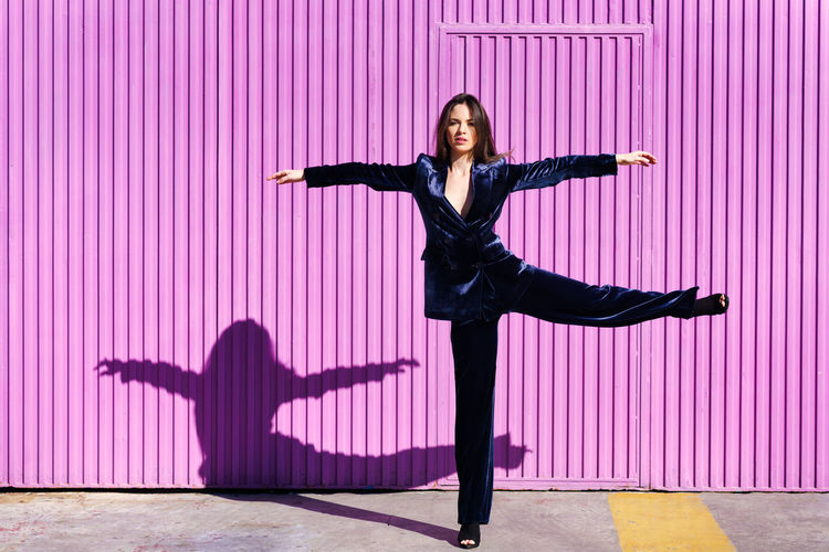 Full length of woman with arms outstretched standing against pink wall
