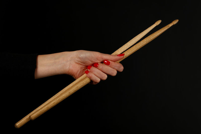 Cropped Hand Of Woman Holding Chopsticks Against Black Background
