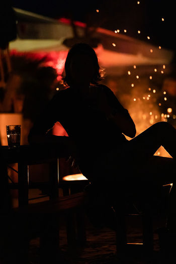 Rear view of silhouette woman sitting at restaurant