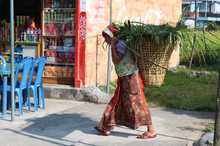 Midsection of woman holding basket while walking outdoors