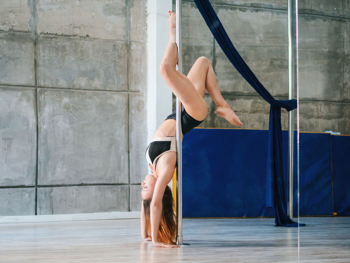 Side view full length of sensuous woman practicing pole dance in studio