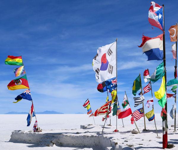 National flags at salar de uyuni against sky