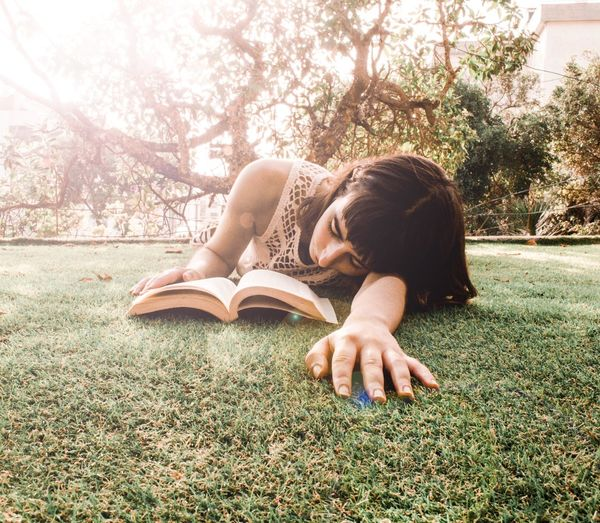 """Books are a uniquely portable magic"" Stephen Hawking EyeEm Selects Young Women Tree Women Relaxation Lying Down Happiness Book Beautiful Woman Natural Beauty"