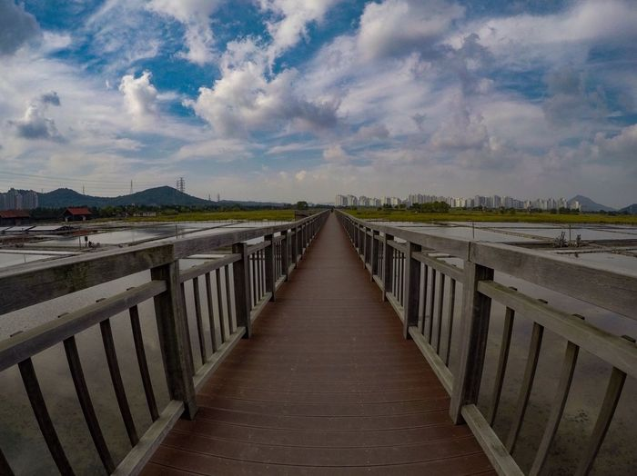 Cloud - Sky Railing Sky Outdoors Day Bridge - Man Made Structure The Way Forward Wood - Material Nature Tranquility Sea Wood Paneling Water Footbridge No People Beauty In Nature