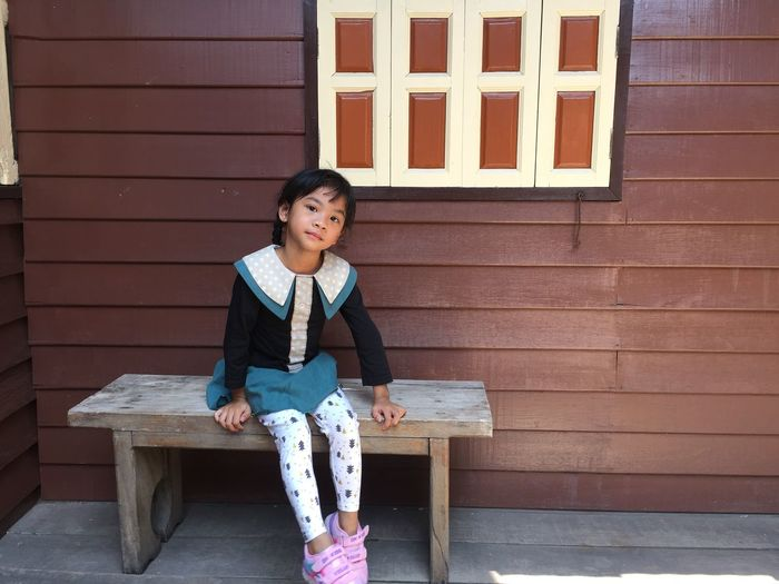 Portrait of smiling girl sitting on bench