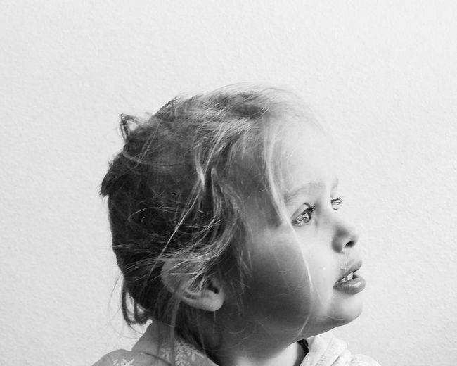 Close-up of thoughtful girl against wall