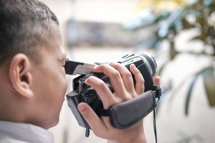 Close-Up Of Boy Using Movie Camera Outdoors