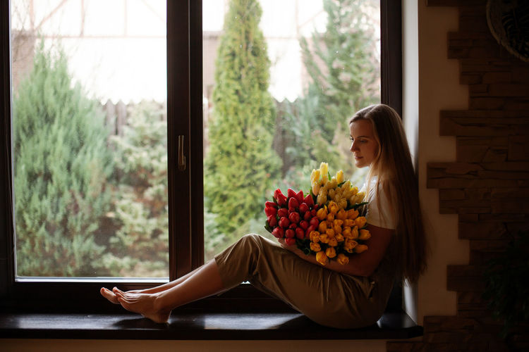 Portrait of a happy girl with a bouquet of multi-colored tulips. women's day, valentine's day,