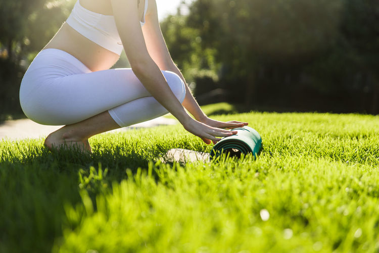 Low section of woman sitting on field