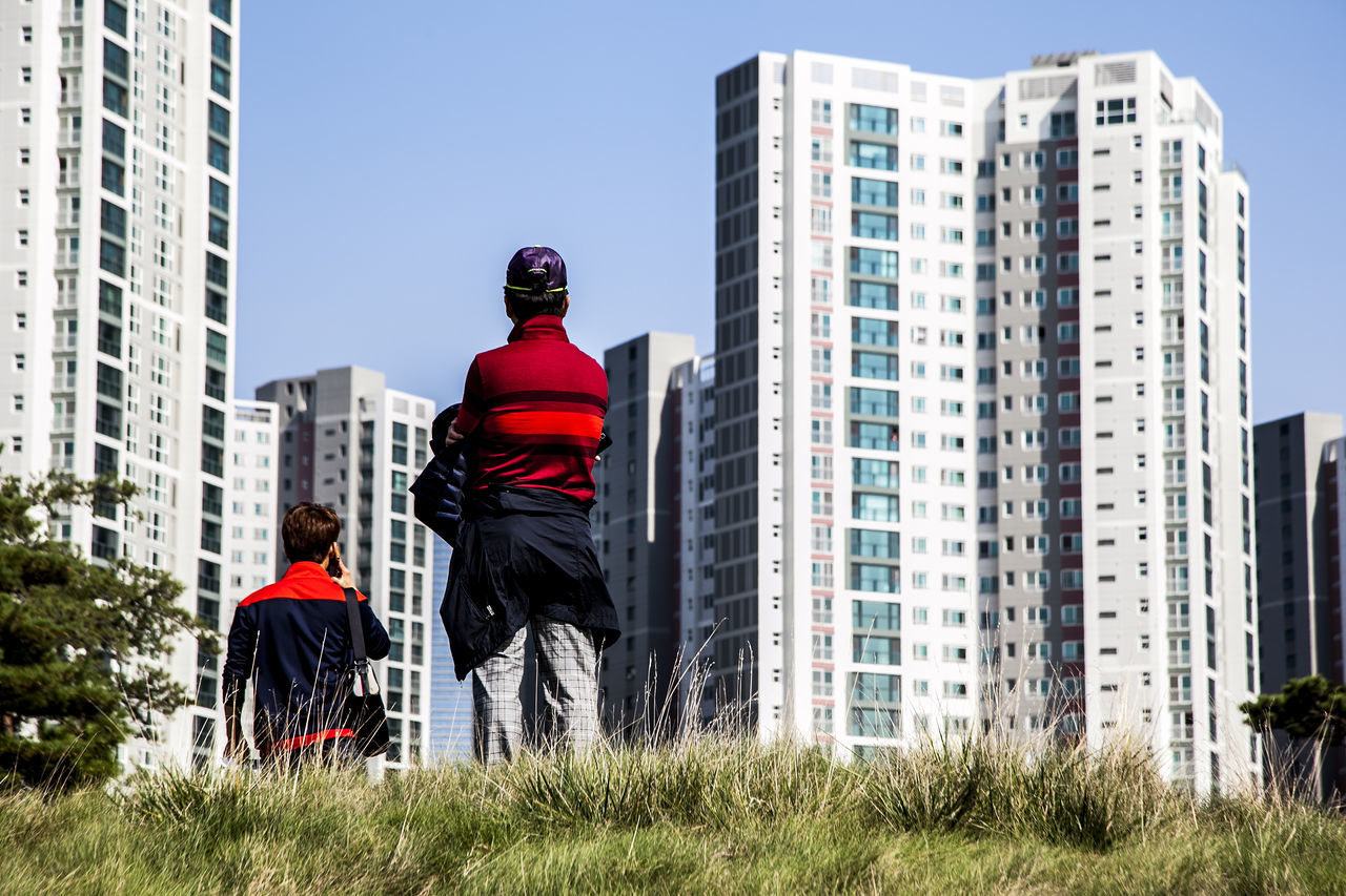 Rear View Of Men Standing On Grassy Field Against Buildings