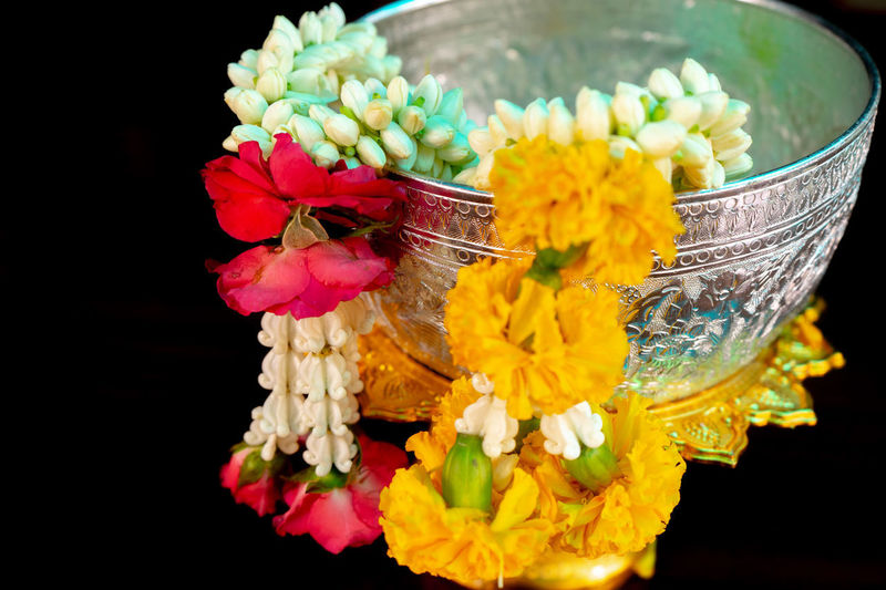 Isolated closeup flower garlands hanging on the edge of silver bowl with black background Freshness Close-up Floral Garland Belief Spirituality Craftsmanship  Traditional And Culture Black Background Isolated Silver Colored Bowl Religion Petal Flower Arrangement Festival No People Nature Vulnerability  Beauty In Nature Marigold Roses Jasmine