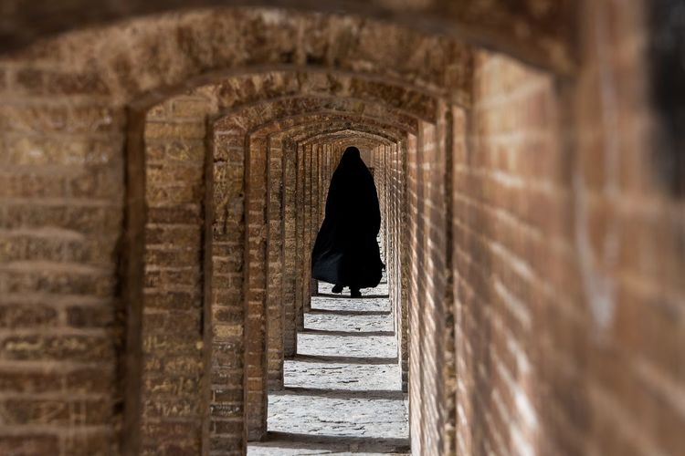 Rear View Of Woman Walking In Corridor At Historical Building