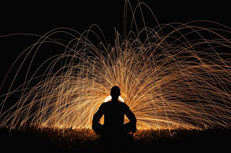 Silhouette man standing by illuminated fireworks against sky at night