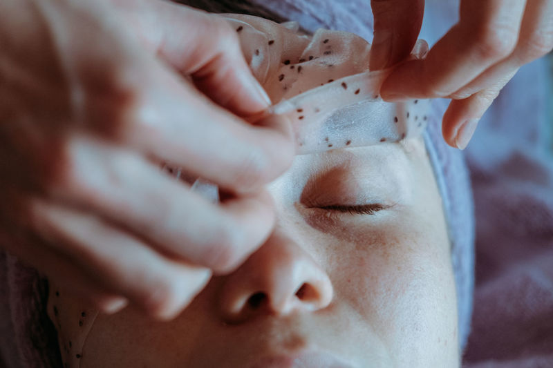 Close-up portrait of young woman applying peel off mask for facial cleansing and spa treatment.