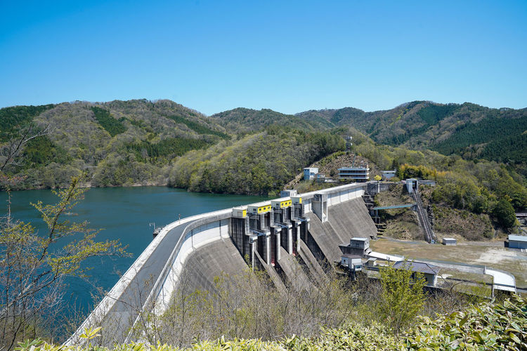 Scenic view of dam against clear blue sky