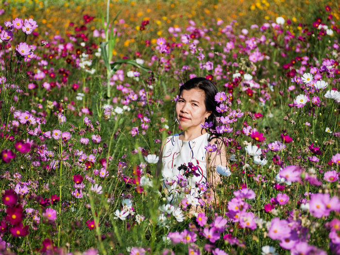 Woman standing on pink flowering plants at field