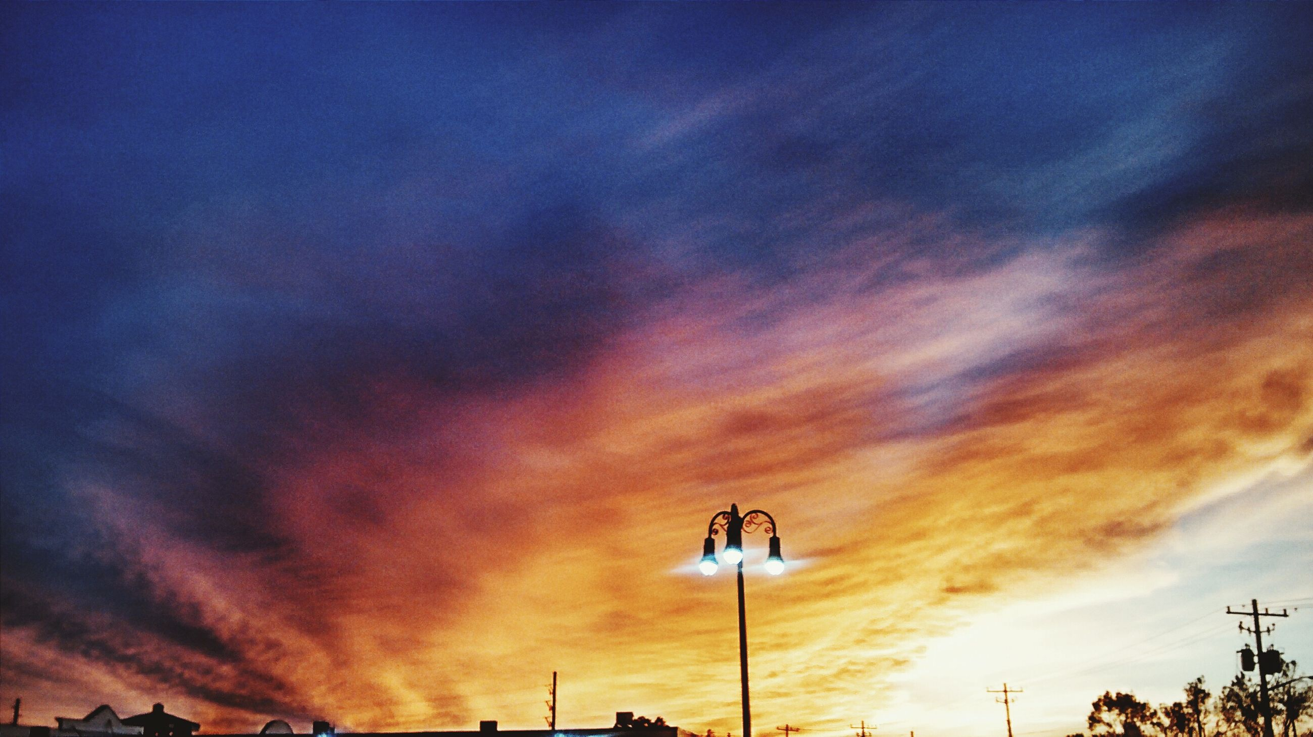 sky, sunset, cloud - sky, low angle view, street light, silhouette, cloudy, lighting equipment, beauty in nature, dramatic sky, weather, nature, scenics, cloud, dusk, overcast, orange color, power line, tranquility, electricity