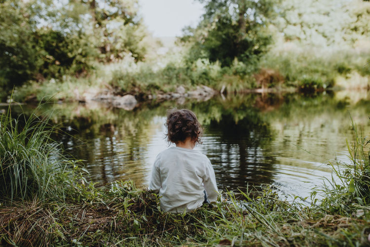 Rear view of child sitting by lake