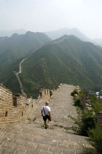Great Wall Of China Huanghuacheng Ancient Ancient Civilization Architecture Backpack Built Structure Day Full Length High Angle View History Leisure Activity Lifestyles Men Mountain Mountain Range Nature One Person Outdoors Real People Rear View Scenics The Way Forward Travel Destinations Walking