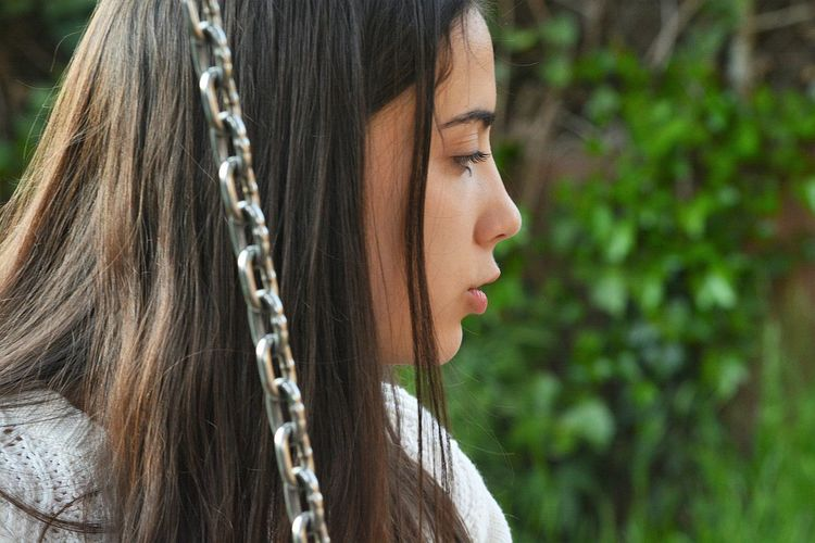 Close-up of woman looking away by metal chain