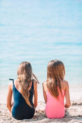 Rear view of women sitting on beach