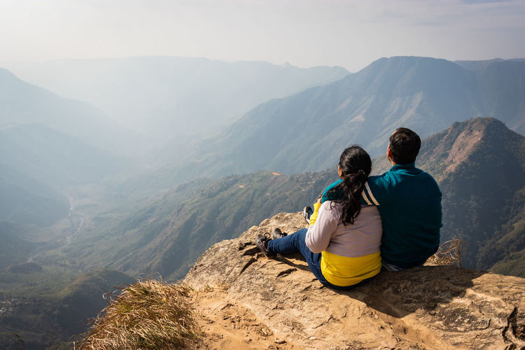 Rear view of couple sitting on cliff against mountains