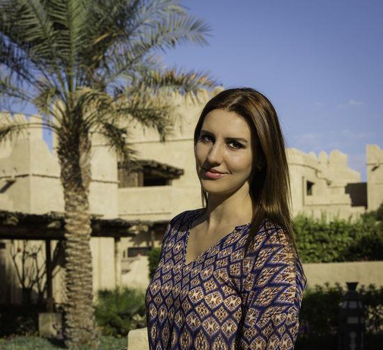 Portrait of smiling woman standing against built structure