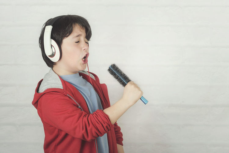 Child Childhood Music Standing Singer  Headphones Music Audio Song Listening To Music Melody Sound Happy People Happiness Earphones Microphone Voice Performance Concert Karaoke Show Concept Portrait Emotion Joy Funny Fun Hair Brush Talent Star Expression Lifestyle Shout Euphoria Feeling