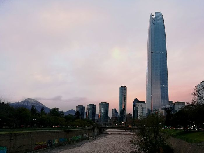 Modern Architecture Skyscraper Business Finance And Industry Cloud - Sky Urban Skyline Sunset Building Exterior No People Built Structure City Sky Illuminated Outdoors Night Cityscape Water Costanera Center Costanera Center Chile Santiago De Chile