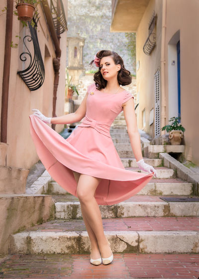 young woman in retro vintage dress City Pinup Retro RetroStyled Stockings Vintage Style Architecture Beautiful Woman Beauty Building Exterior Clothing Dress Fashion Hairstyle Lifestyles One Person Outdoors Pink Color Portrait Real People Retrofashion Vintage Women Young Adult Young Women