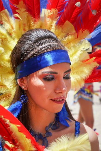 Portrait of young woman with multi colored feathers