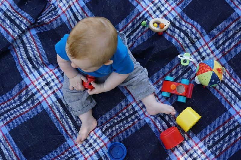High angle view of baby boy playing with toys on blanket