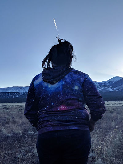 Woman walking against clear blue sky