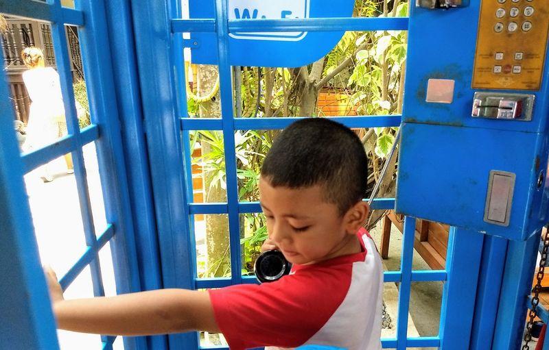 Boy talking through pay phone