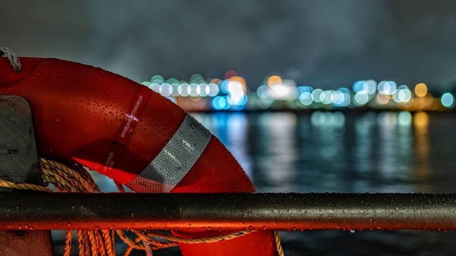 Close-up of lifebelt on railing at night