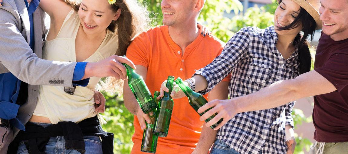 Friends Toasting Bottles Against Tree