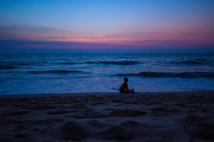 Silhouette boy playing at beach against sky during sunset