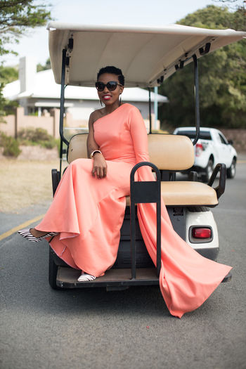 Portrait Of Smiling Young Woman Sitting On Golf Cart