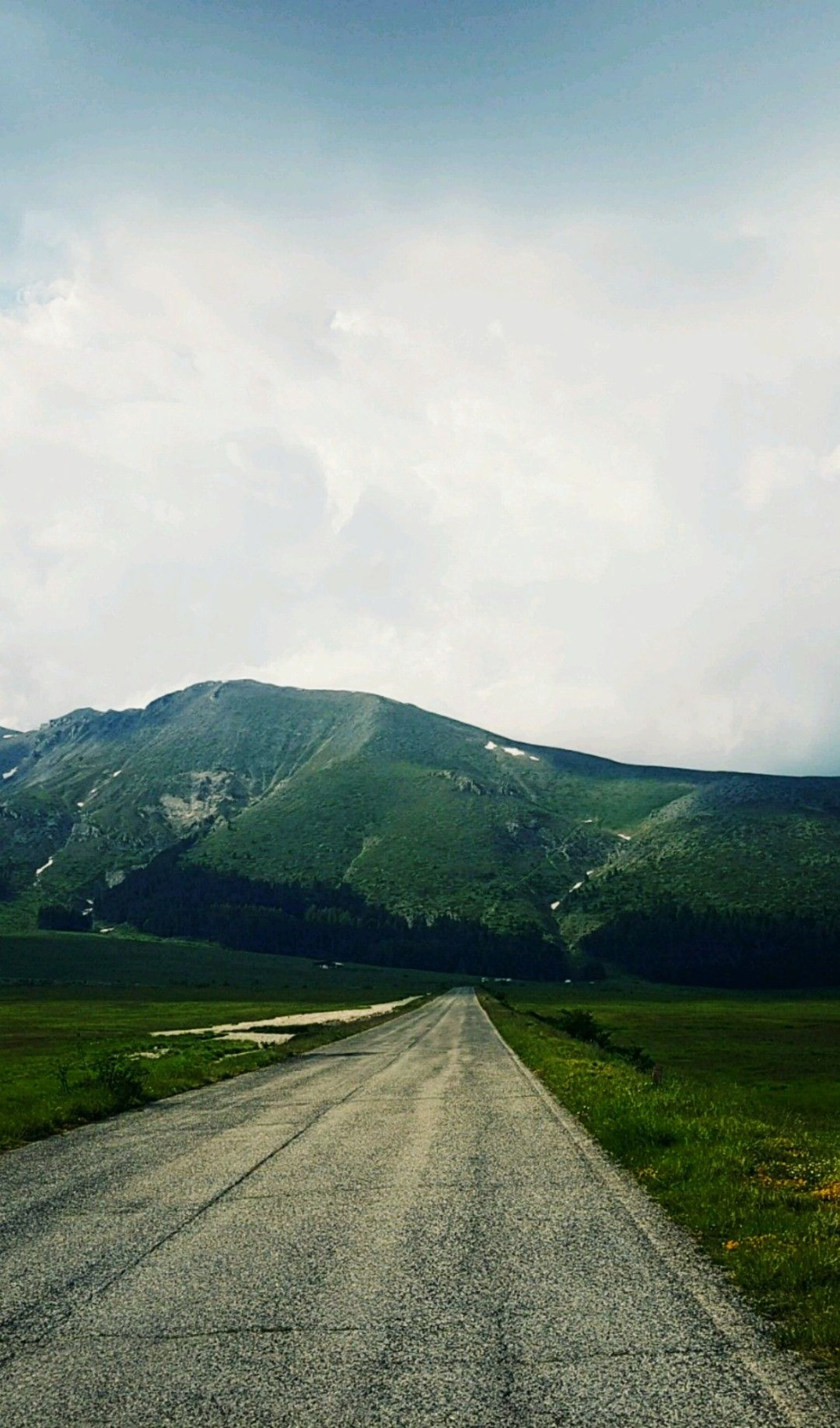 road, sky, direction, landscape, cloud - sky, the way forward, transportation, mountain, environment, tranquility, beauty in nature, tranquil scene, nature, no people, day, scenics - nature, non-urban scene, diminishing perspective, grass, plant, outdoors, long, mountain range