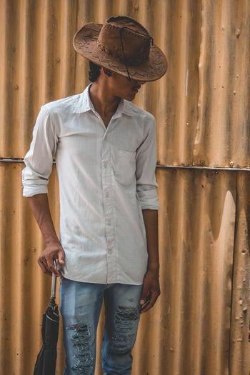 Teenage Boy Wearing Hat Standing Against Corrugated Iron