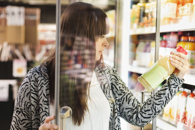 Midsection of woman holding ice cream at store