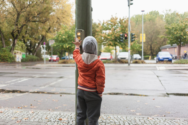 Rear View Of Boy Pressing Push Button On Pole While Standing On Footpath