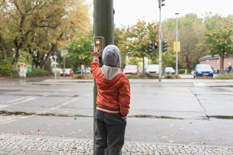 Preschool boy pushing button of traffic lights in urban street environment Boy Button Child Children City City Life Light Orange Preschooler Pressing Pushing Street Traffic Traffic Lights Urban Vest