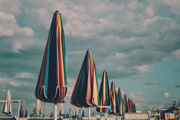 Low angle view of beach umbrellas against cloudy sky