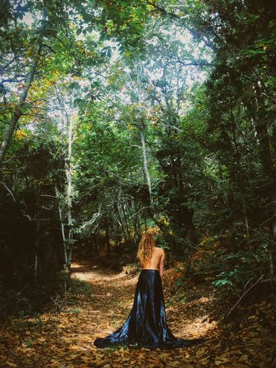 Rear view of shirtless woman wearing skirt while standing amidst forest