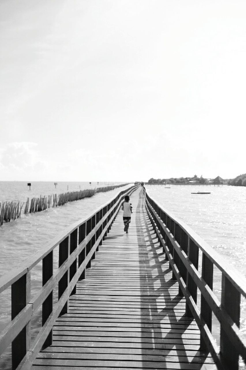 sea, pier, horizon over water, railing, water, beach, full length, jetty, outdoors, day, wood - material, nature, leisure activity, one person, real people, clear sky, vacations, footbridge, tranquility, wood paneling, the way forward, men, sand, summer, scenics, standing, lifestyles, sky, beauty in nature, adult, one man only, only men, people