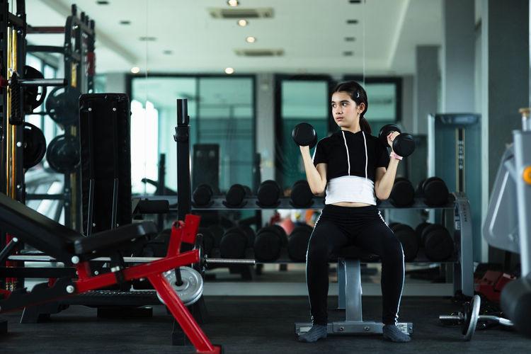 Full length of girl exercising at gym